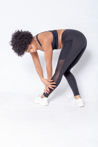 Shakolo crossover bra in black and mid waist leggings in black side view model bending over and model touching leg