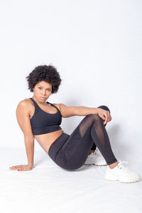 Shakolo crossover bra in black and mid waist leggings in black side view model sitting on floor