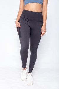 Shakolo high neckline bra in dark blue and high waist leggings front view with hand in a pocket