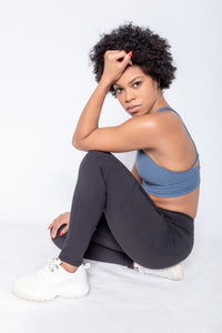 Shakolo high neckline bra in dark blue and high waist leggings side view with model sitting on the ground