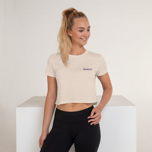 Flowy crop top with the words Shakolo Exceed Expectations embroidered on the left side in light beige color