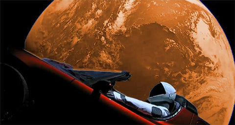 starman riding elon musk's tesla roadster in front of earth