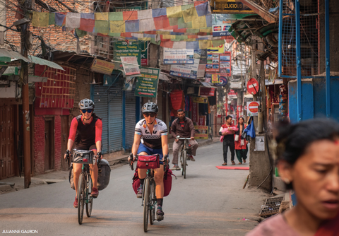 Jennifer Gurecki and Roz Groenewoud biking through the streets of Nepal.