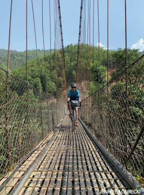 Roz Groenewoud cycling across a rickety bridge in Nepal.
