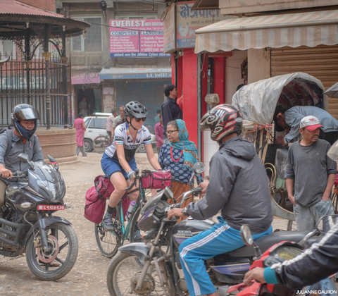 Jennifer Gurecki biking through traffic in Nepal.