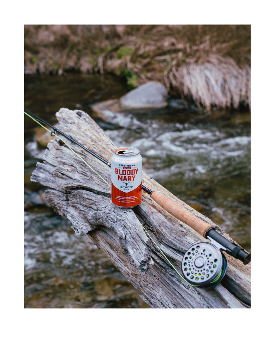 Load image into Gallery viewer, Cutwater Spicy Bloody Mary Canned Cocktail next to a fishing pole