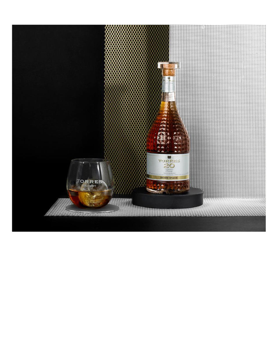 Load image into Gallery viewer, Torres 20 Brandy bottle on shelf with glass