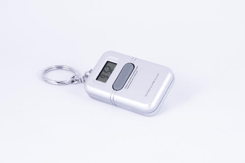 A silver, rectangular, hand-held digital clock on a keychain, with one central button to request audible time.
