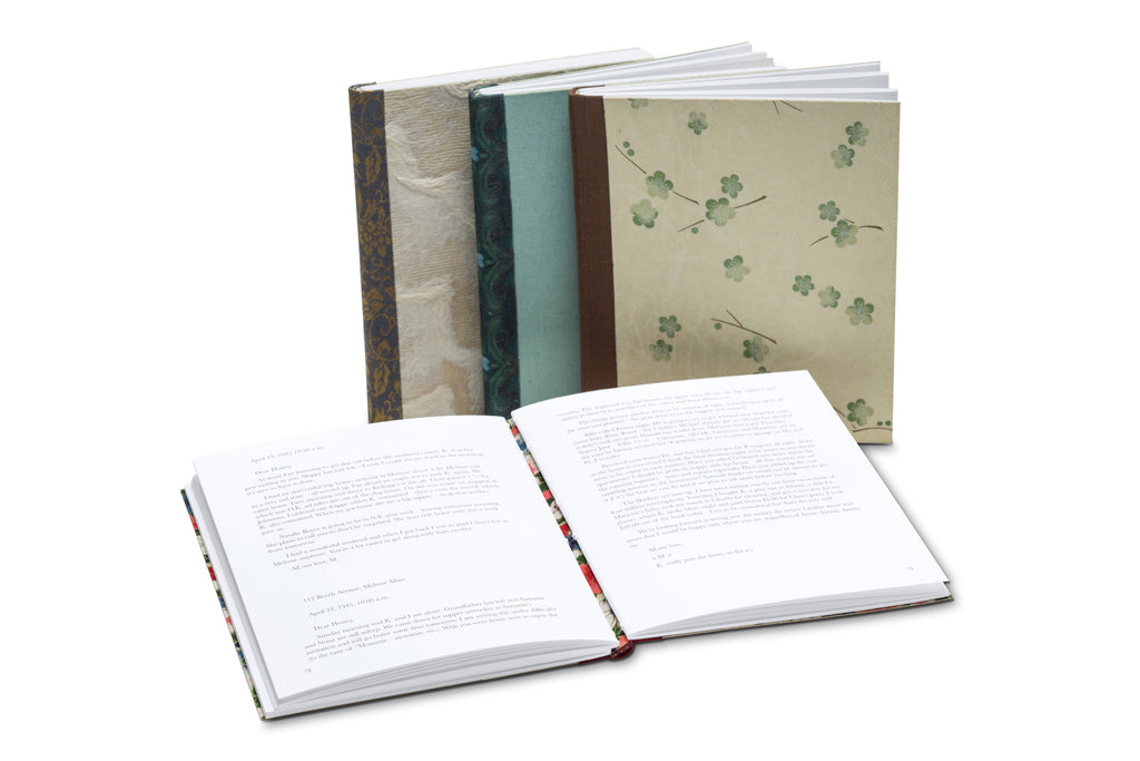 4 books pictured on a white background. 3 books are standing up, closed. 1 book is displayed open.