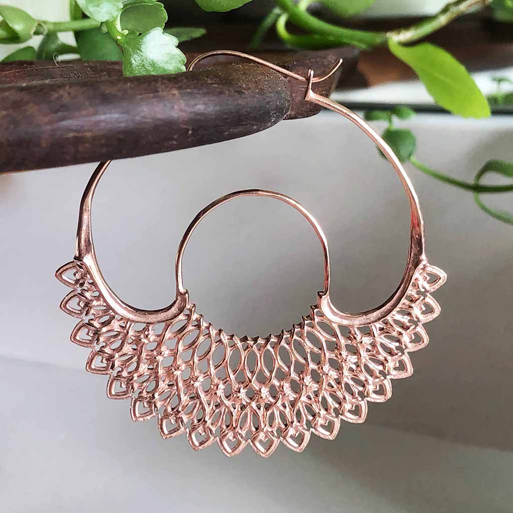 Ethical made rose gold statement hoops. Round with a web or lace like design on the lower half