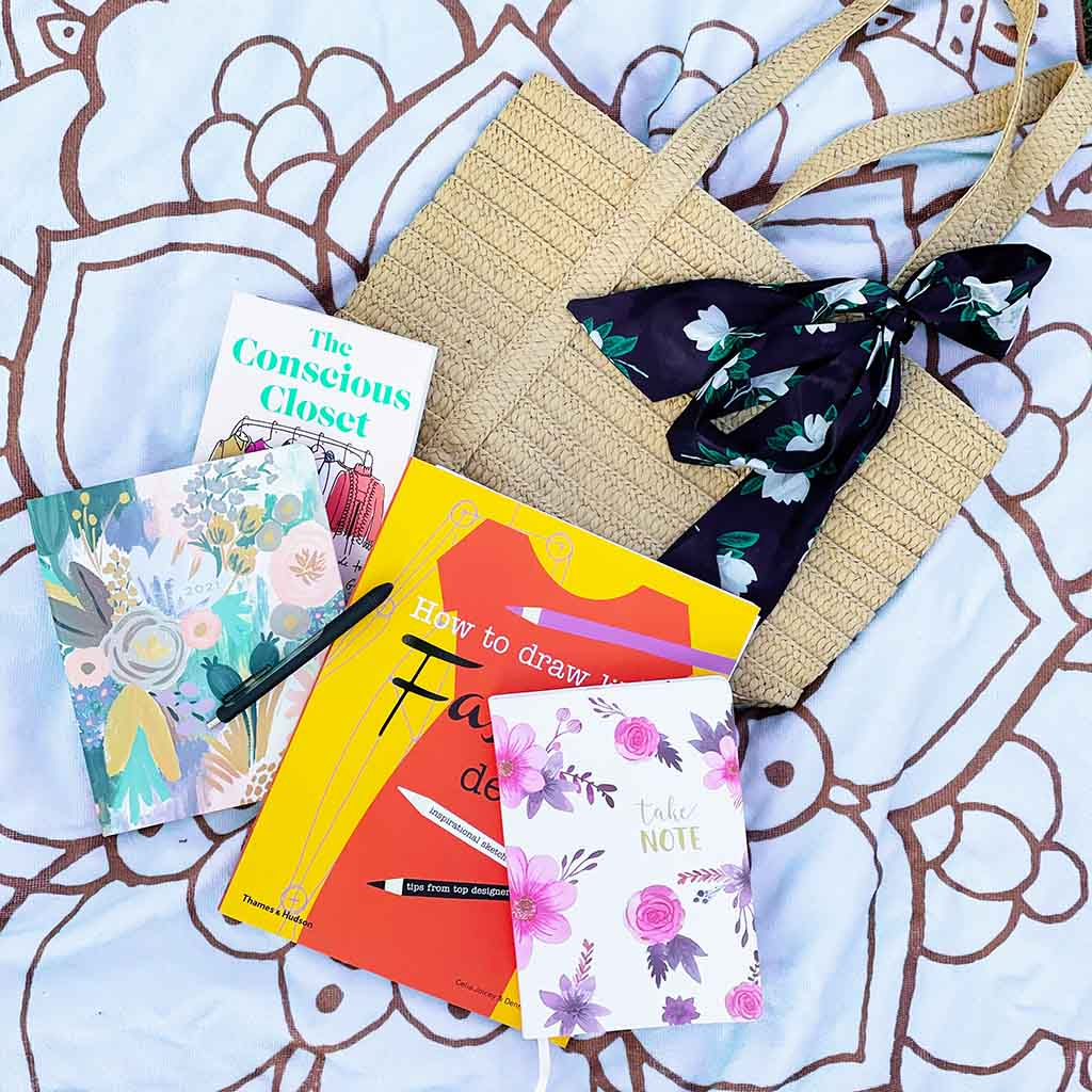 Books on Sustainable fashion and a writing journal on a blanket