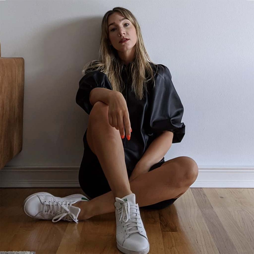 women capsule wardrobe expert Anna Dunbar sitting on a hardwood floor wearing monochromatic black outfit and white sneakers