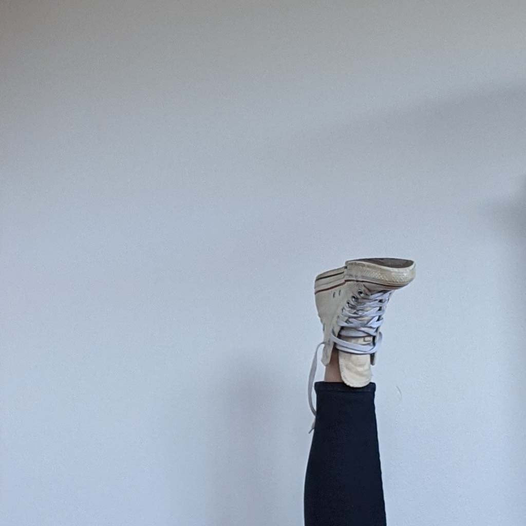 Capsule Wardrobe shoes. Converse sneakers and leg in front of white wall