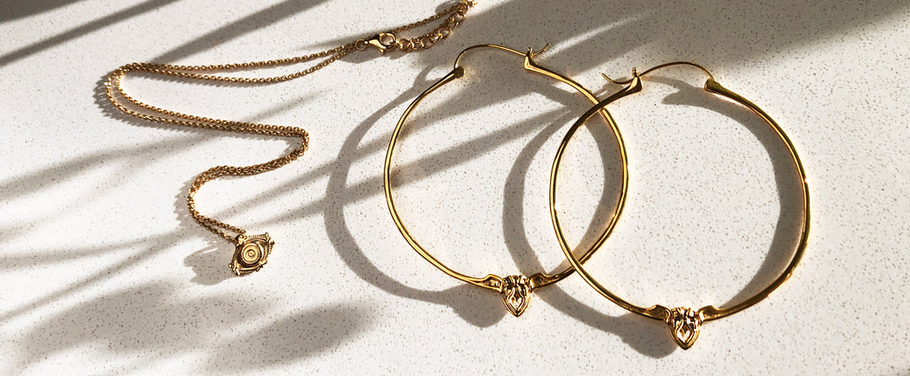 Astor + Orion ethically made jewelry. Gold hoop earrings and eye protection charm pendant in sunlight