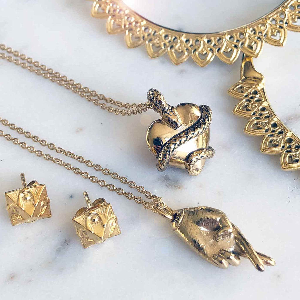 sustainable fashion jewelry, gold charm necklaces, gold hoop earrings, and gold pyramid studs