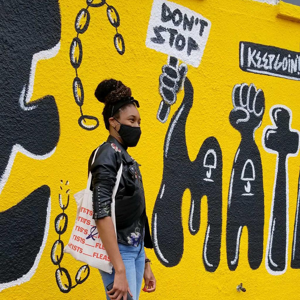 """Podcast Host on Fashion standing in front of a bright yellow and black mural with the words """"don't stop"""" and """"keep going"""""""