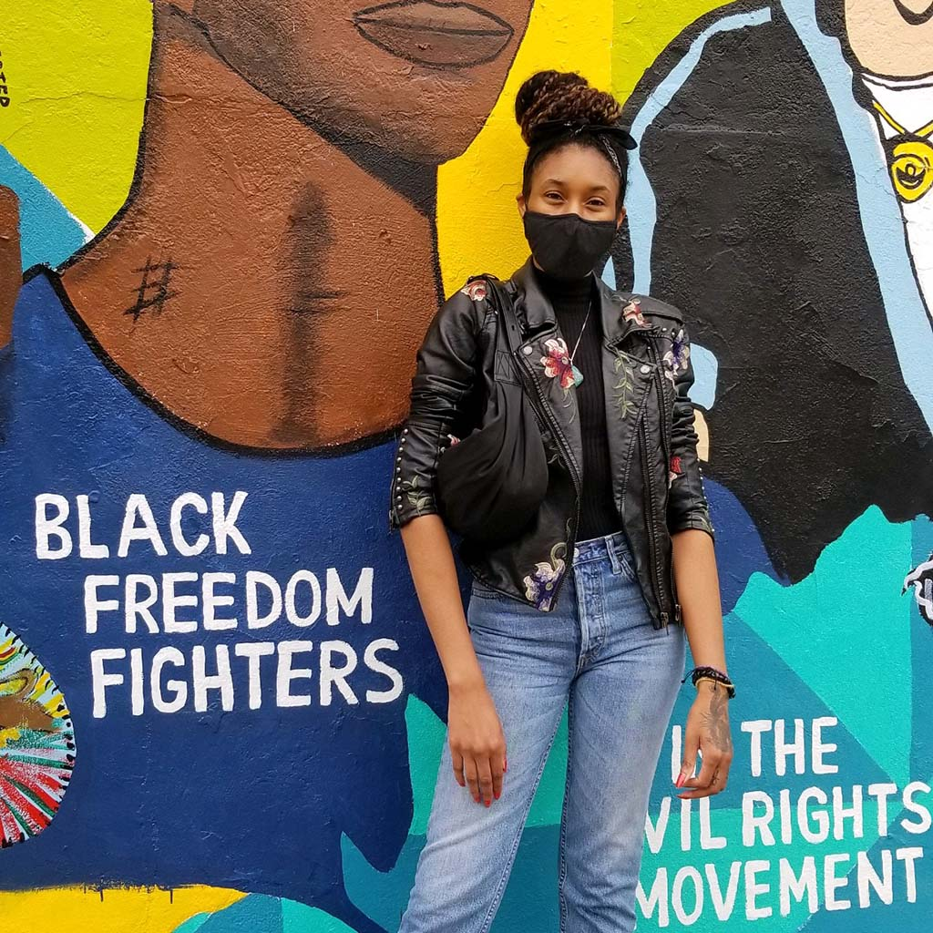 """Black Podcast host in front of mural about the Civil Rights Movement. It features colorful art of black historic figures and has the words, """"Black freedom fighters"""" and """"the civil rights movement"""""""