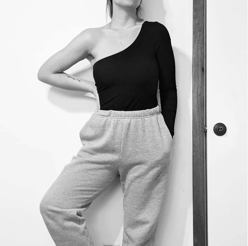 wardrobe capsule for women. Example of comfortable choices, sweatpants and one shoulder body suit