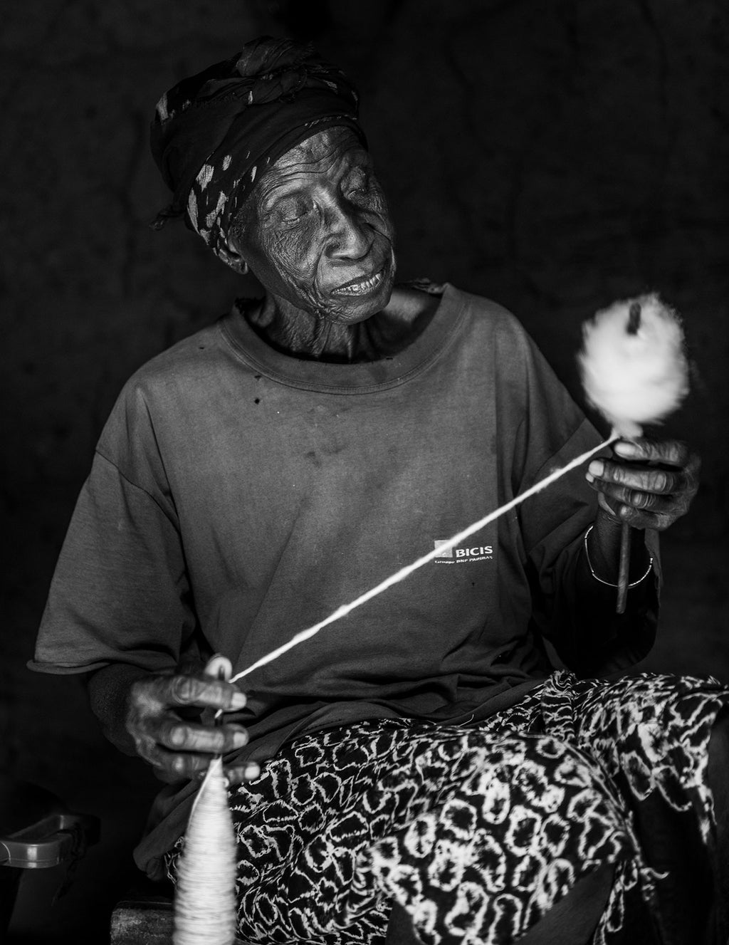 old lady creating cotton thread from organic cotton ball on a stick