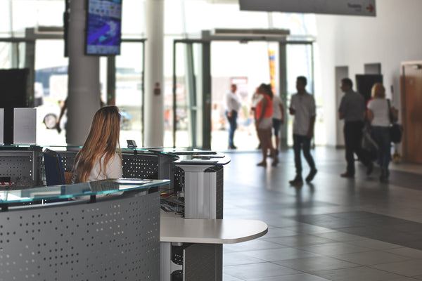 Woman sitting behind a security desk in a busy airport
