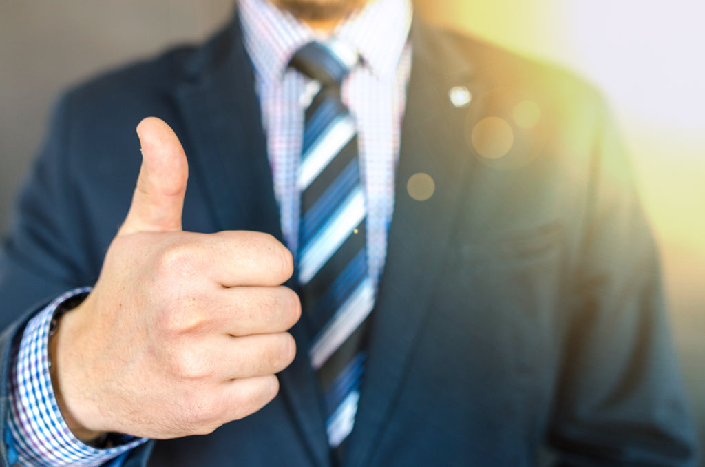 close up photo of man wearing black suit jacket doing thumbs