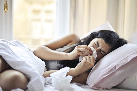 sick woman lying in bed with runny nose