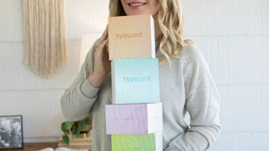 Woman holding stack of four boxed diffuser refills