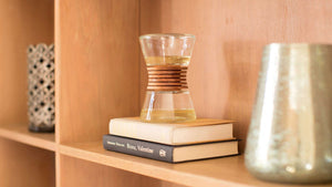 Diffuser sitting on top of two books in a wooden bookshelf