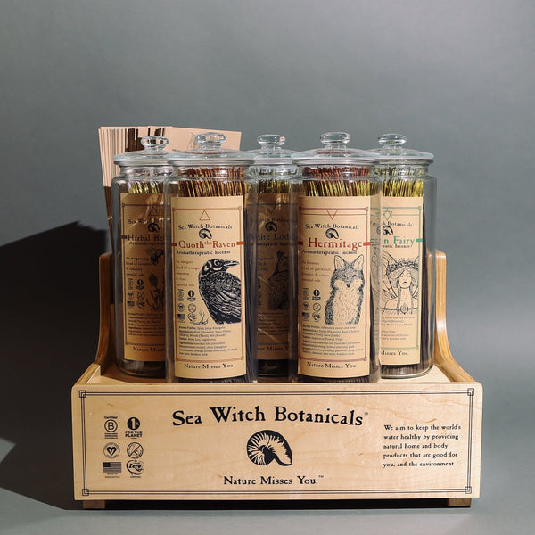 Front view of small incense set with optional wood display base. Set includes 5 branded glass jars and lids with incense and branded envelopes