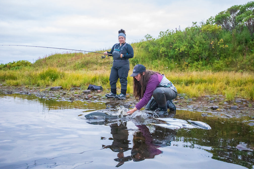 Guide, Elise Adams, releases a coho for another happy angler on the Egegik River, something she's been doing for three years with Becharof Lodge.