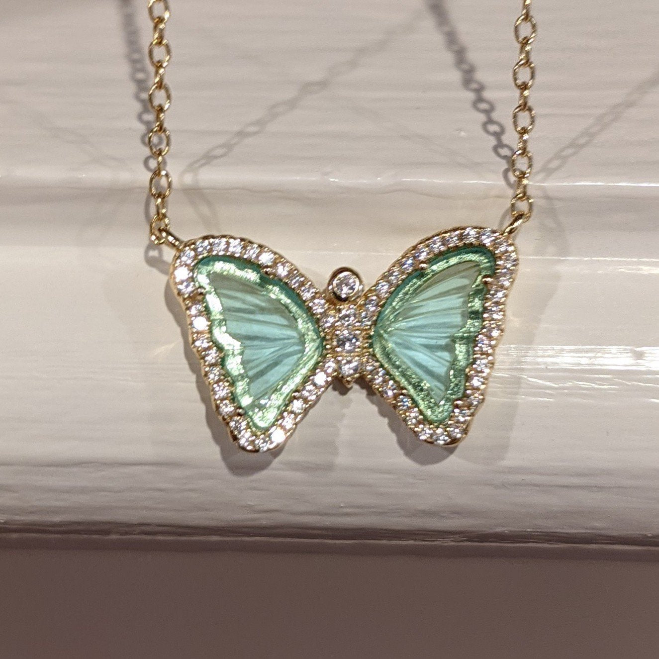 Mini gemstone butterfly necklace in aqua green and yellow gold