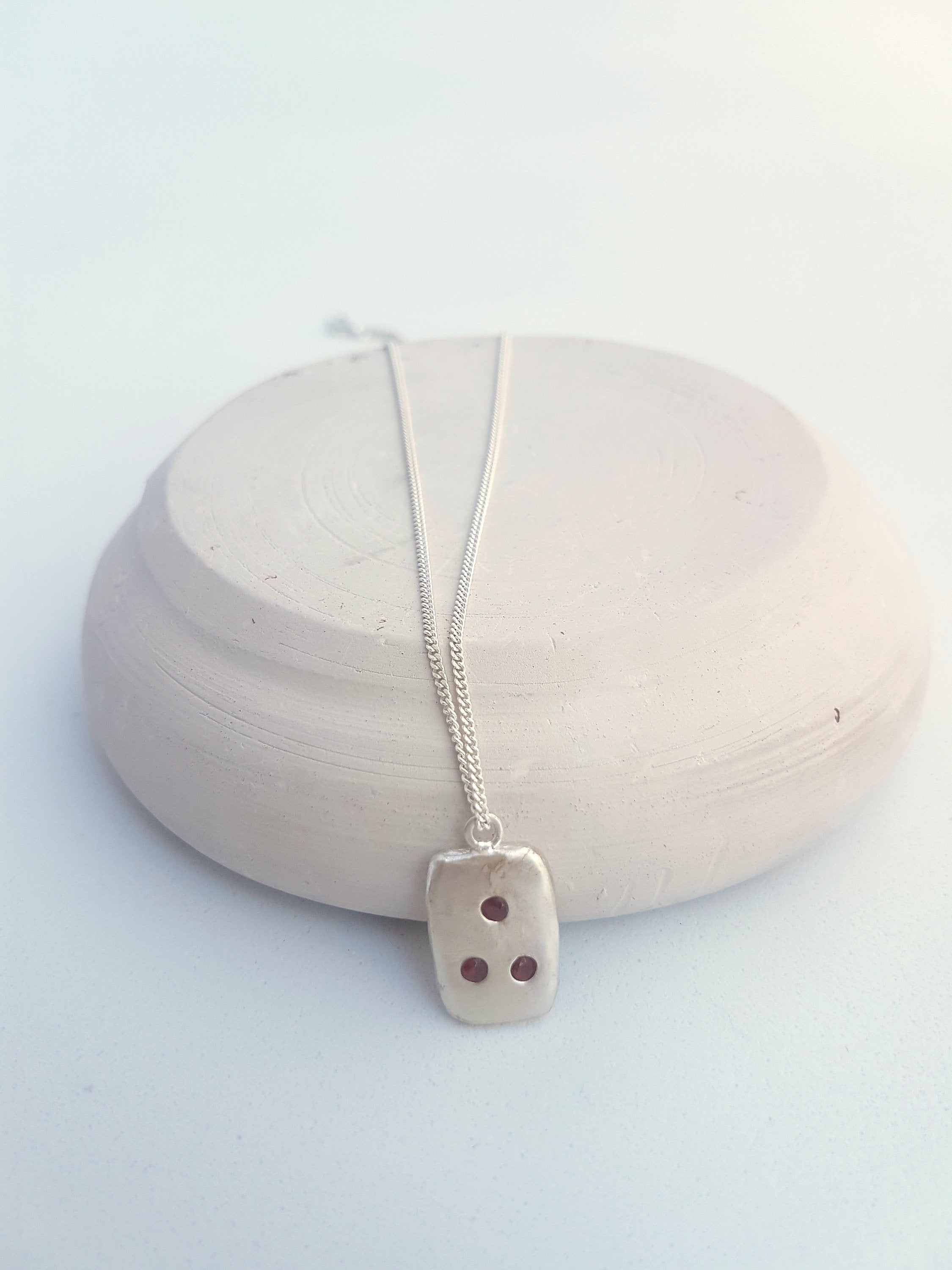Geometric pendant necklace in sterling silver with garnets. Dainty rectangular pendant for a contemporary woman.