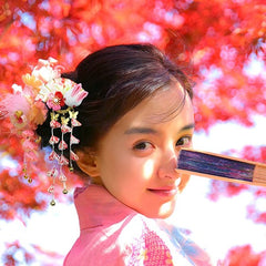pretty girl wearing japanese hair accessory and holding japanese hand fan
