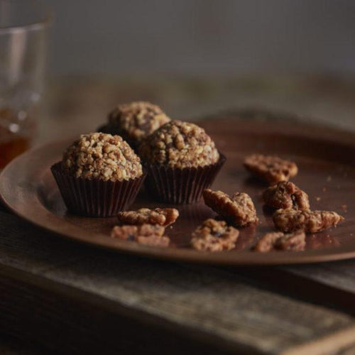 Hooch is handcrafted with Belgian bittersweet chocolate, toasted pecans and Union Horse Distilling Co. Reserve Bourbon.  Finished in a caramelized pecan crunch - brown sugar, maple syrup, butter and cayenne pepper. Southern Pecan Praline.  Kansas City Gifts.  Kansas City Chocolates.  Bourbon Chocolate.