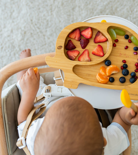 Child with bamboo elephant suction plate and grapes cut lengthways