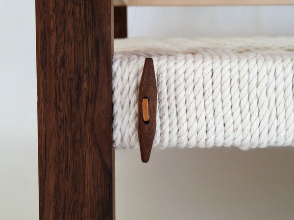 Handcrafted walnut toggle of dog bed to keep wool topper in place