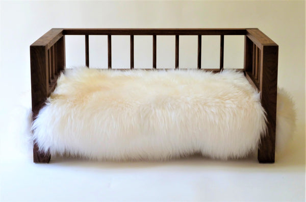 Walnut Belvoir Slumber Wolf dog bed with white wool topper viewed from the front