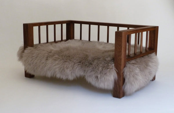 Walnut Belvoir Slumber Wolf dog bed with stone wool topper viewed at an angle