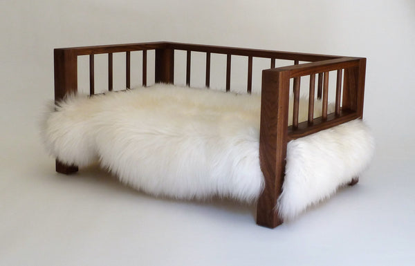 Walnut Belvoir Slumber Wolf dog bed with white wool topper viewed at an angle