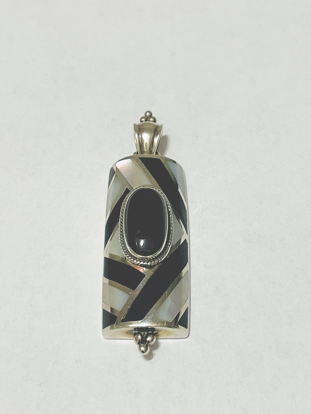 This lovely pendant consists of a lovely Mother of Pearl and Black Onyx design with a large Onyx stone in the middle.  It measures 2.75 X 1.24 inches.  We include a complimentary Sterling Silver chain to complete the over all look.