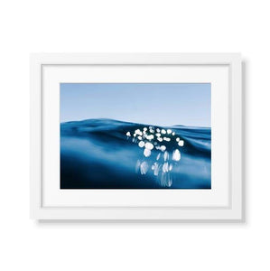 Framed fine art print of the ocean with light that looks like a jellyfish
