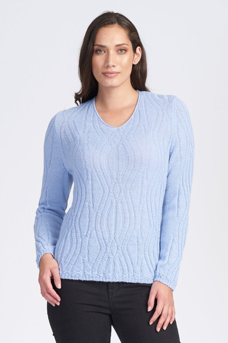 Woman wearing a long sleeve jumper with V neck. 100% Baby Alpaca fibre. Soft wavy pattern. Hip length.Hypoallergenic.