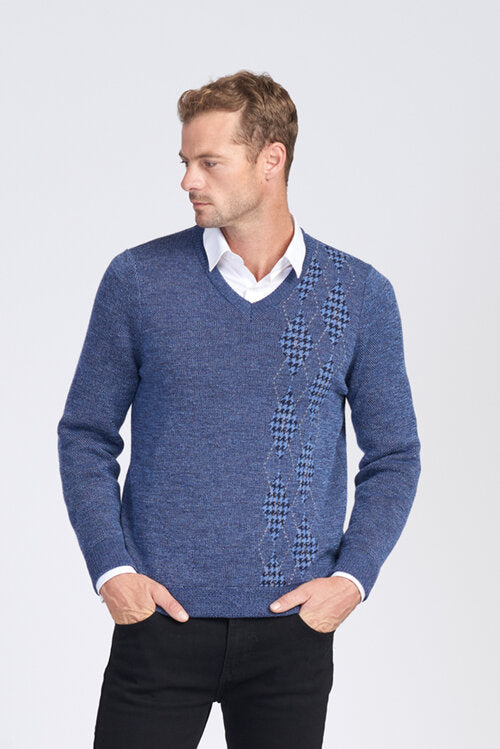 Man wearing a blue  V neck jumper. Long sleeves with houndstooth and argyle style patterning down the left front of the jumper. Alpaca wool knit.