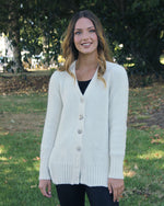 Womens' long sleeve cardigan. Feature buttons down front with ribbed cuffs and ribbed hem with split sides. Alpaca wool.