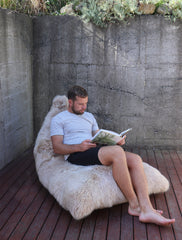 Sheepskin lounger with person sitting in it reading a book.