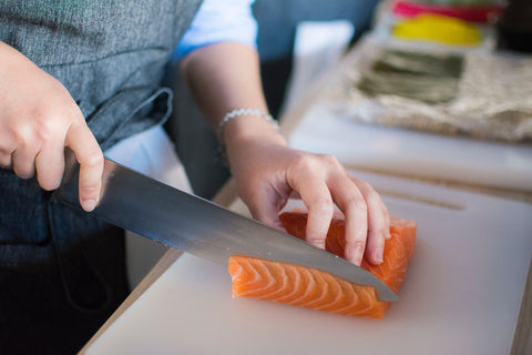 someone slicing salmon | The Best Vitamins for Your Skin