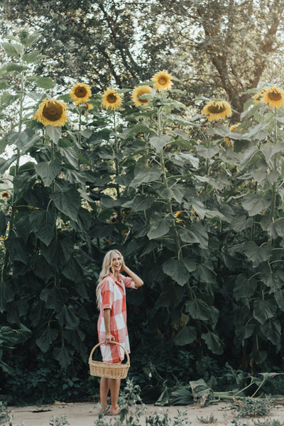 girl standing amongst sunflowers | Our Favorite Ways to Reduce Redness on Your Face