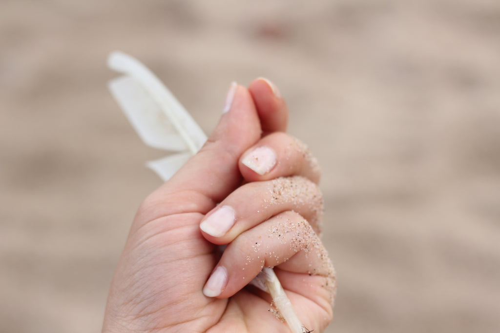 hand holding feather with sand on it | Get Dry Hands in the Winter? Same, Girl