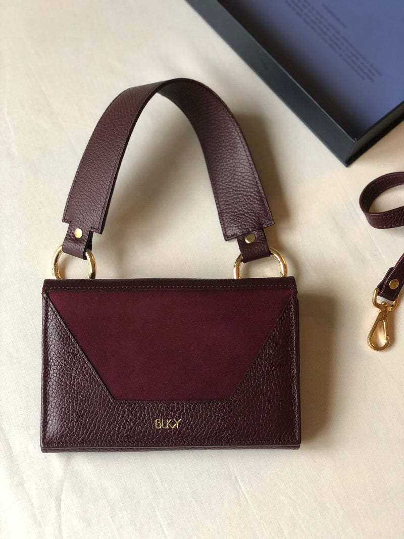 Purple multifunctional bag with gold details and a purple wide strap with gold details