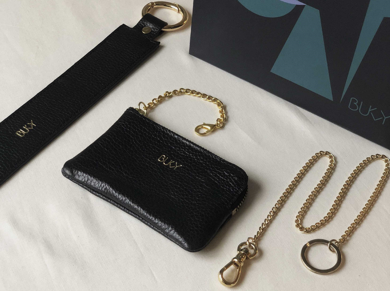 Small black wallet with gold details, gold plated key chain and a black wide strap with gold details